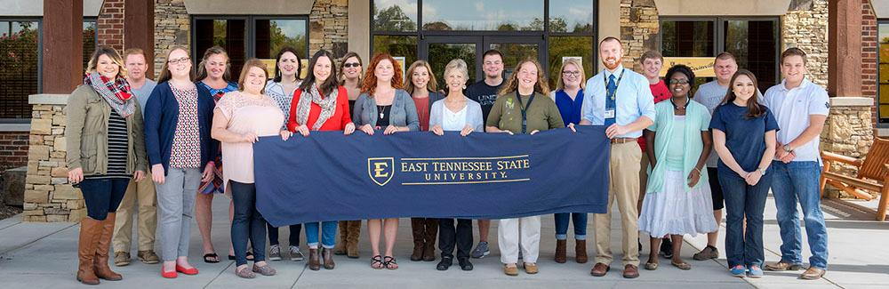 ETSU Sevierville faculty and staff holding an ETSU banner.