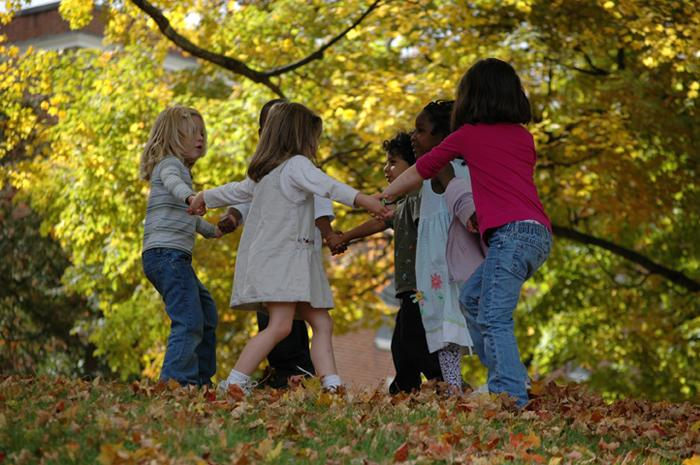 Children playing in leaves.