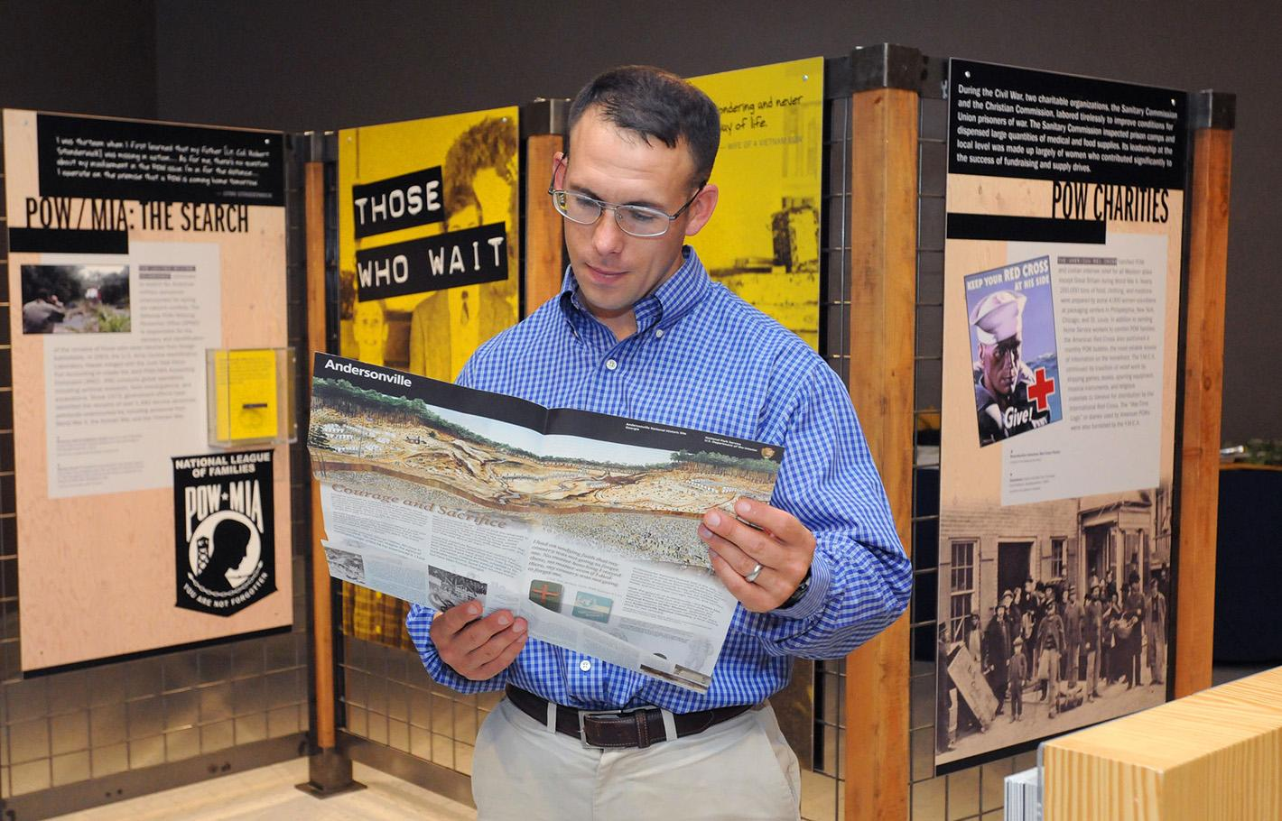 A visitor views supporting material in the 2015 traveling exhibition Victory from Within: The American Prisoner of War Experience.
