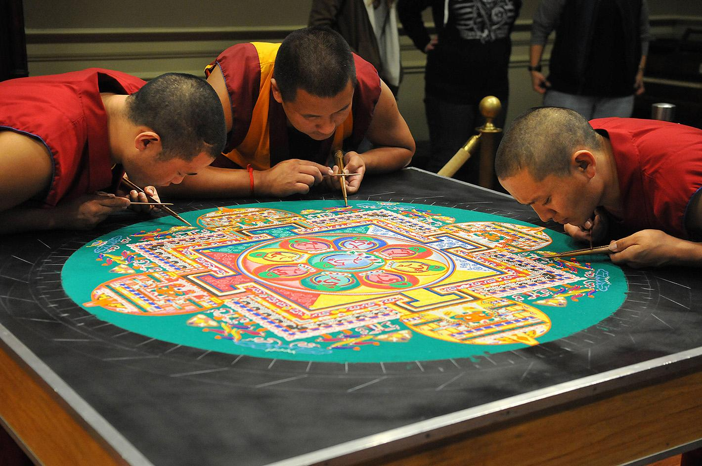 Tibetan monks creating a sand mandala. The monks were at the museum in 2014 as part of a visit sponsored by the Mary B. Martin School of the Arts.